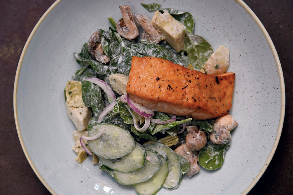 Pan-seared Scottish salmon over a salad of baby spinach and artichoke hearts with a lemon-dill crème fraîche