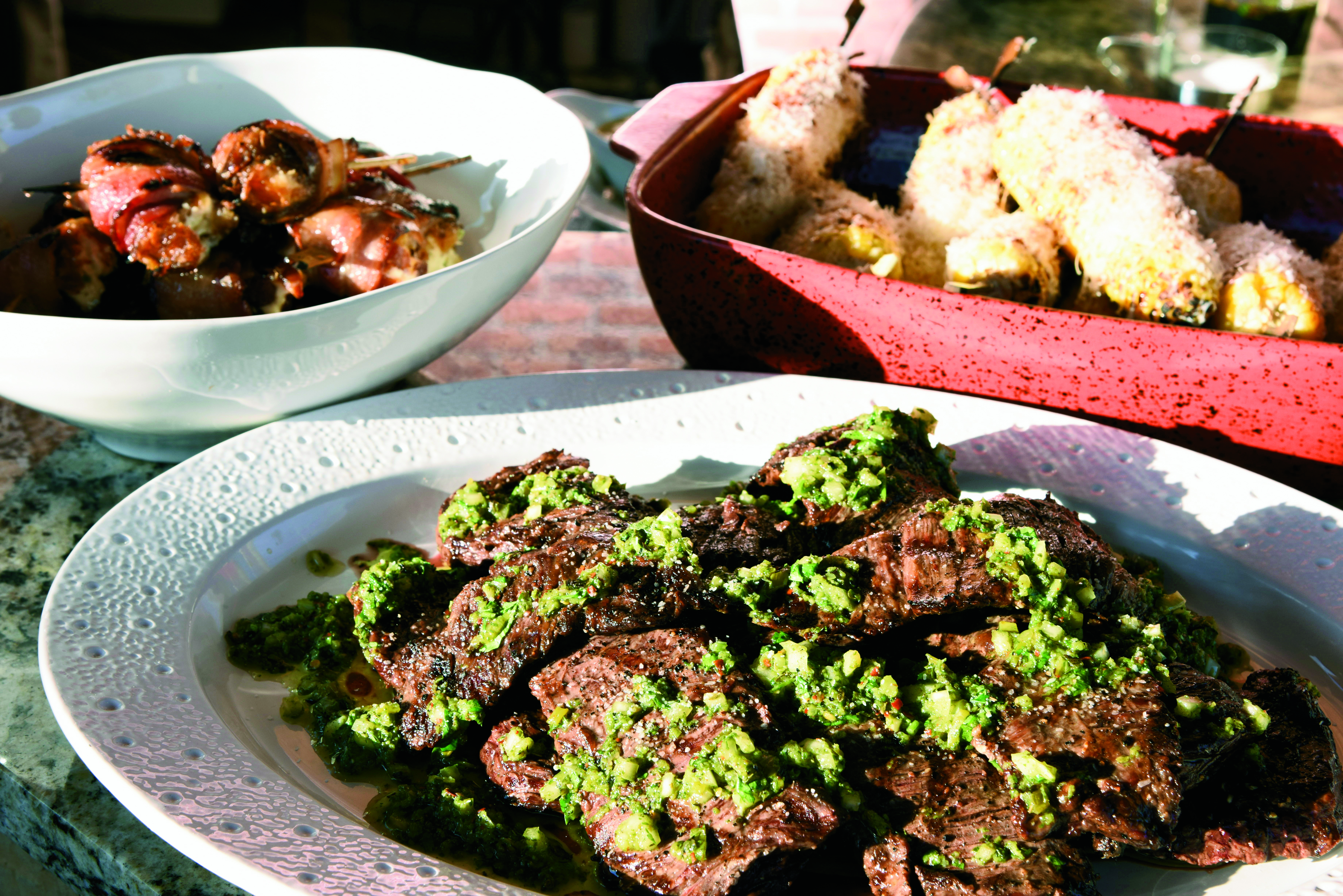 (clockwise from left) Stuffed dates. Mexican-style corn on the cob, Carne asada with chimichurri sauce