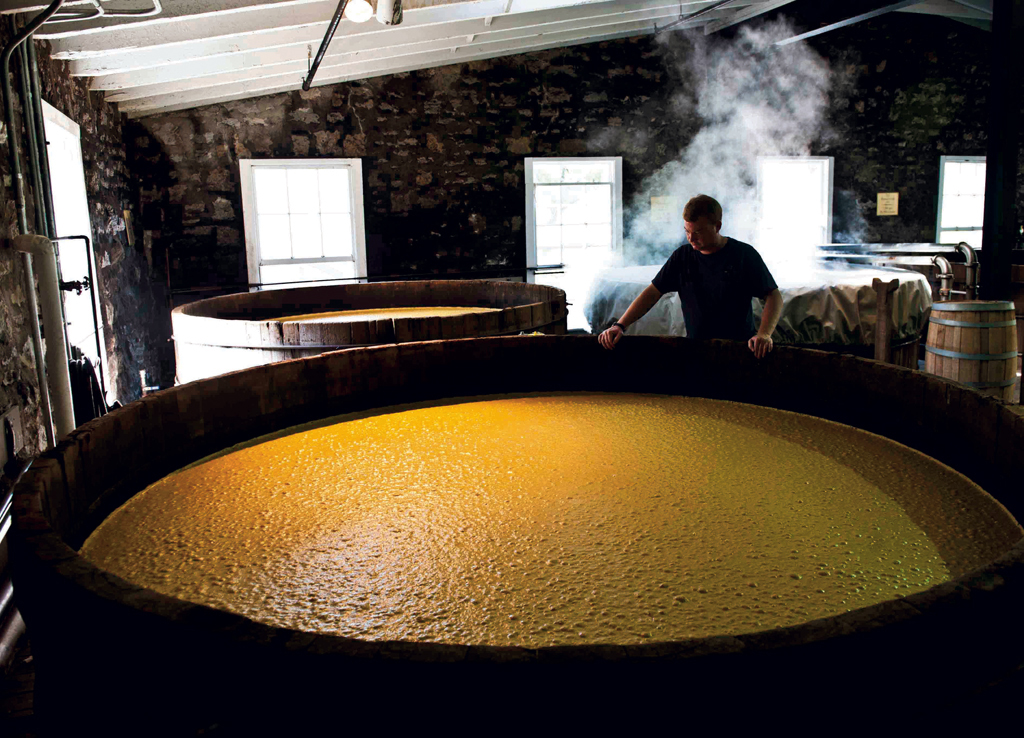 In large cypress fermenting tubs, the mash bubbles as the yeast converts sugar into alcohol.